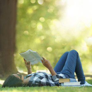 Shot of a young woman lying on grass and reading a book